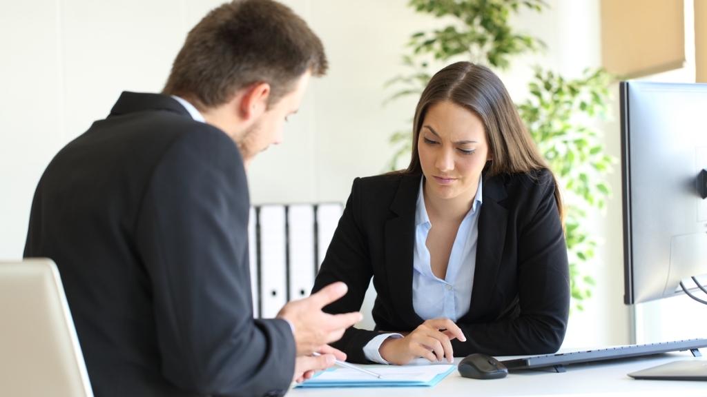 Man giving woman difficult feedback.