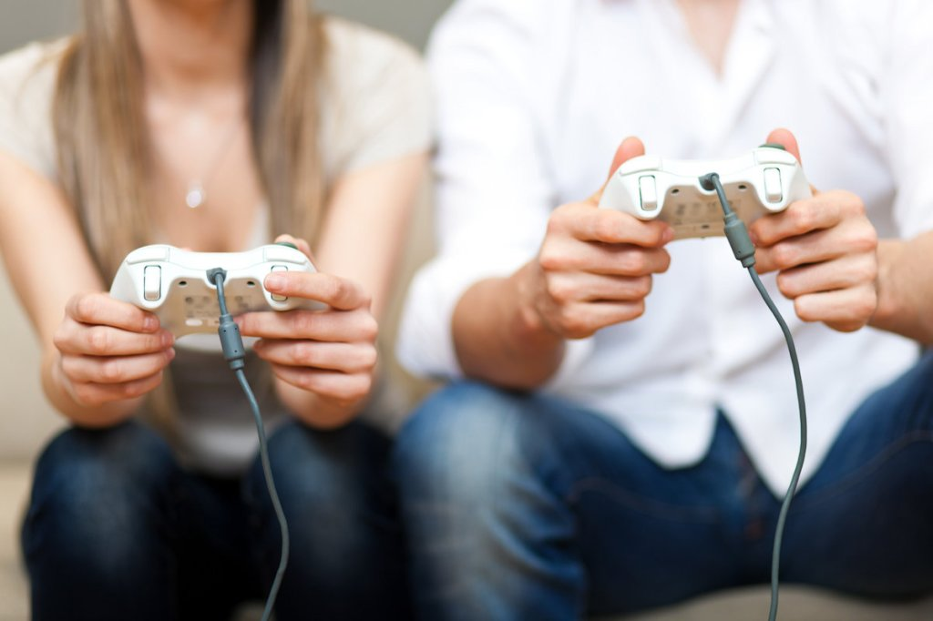 Woman and man seated on a couch playing a video game.