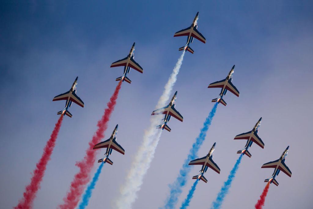 Aerobatic jets with coloured smoke trails.